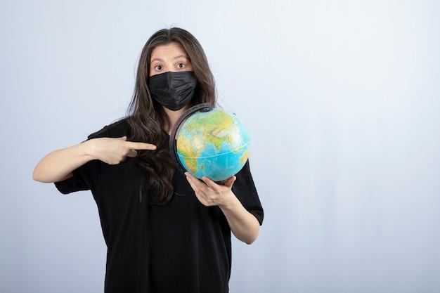 Donna castana con capelli lunghi nella mascherina medica che indica al globo del mondo.