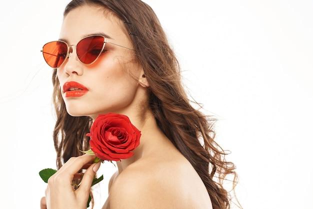 Donna castana con rosa rossa e occhiali da sole