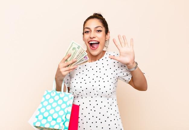 Donna bruna con borse della spesa e soldi allegramente agitando la mano