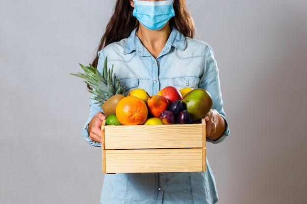Donna castana con mascherina chirurgica che consegna scatola piena di frutta