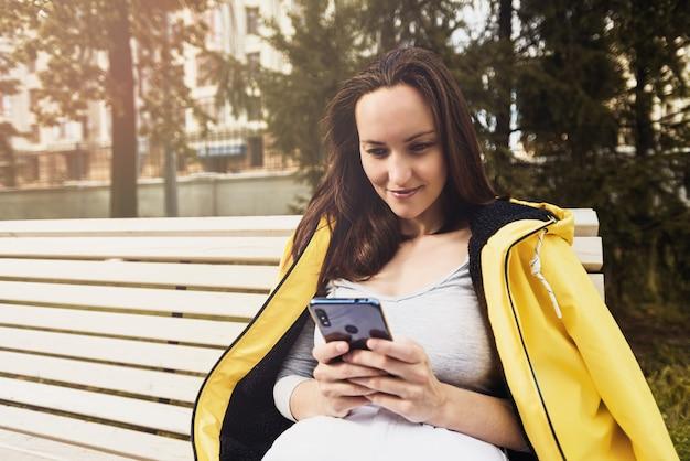Donna castana in giacca gialla con lo smartphone nelle sue mani seduto sulla panchina