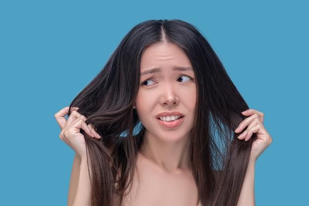 Giovane donna asiatica castana che tiene i suoi capelli e che si sente stressato
