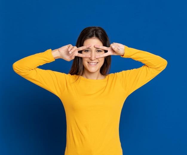 Giovane donna castana che gesturing sopra la parete blu