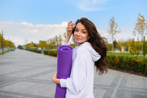 La giovane donna castana in abiti sportivi bianchi con gli auricolari tiene il tappetino viola e guarda indietro sullo sfondo del parco cittadino