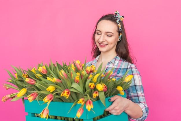 Giovane donna castana con mazzo di tulipani su sfondo rosa