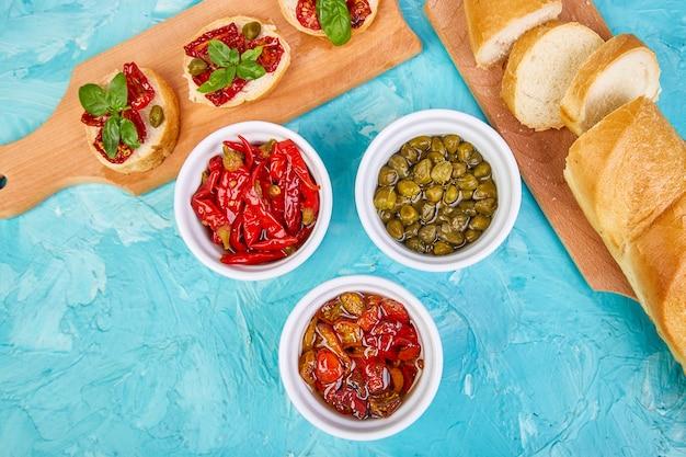 Bruschette o crostini con pomodori secchi e capperi.
