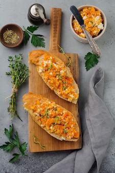Bruschetta con zucca al forno, formaggio feta e timo su pietra grigia o sfondo concreto panino di zucca piccante