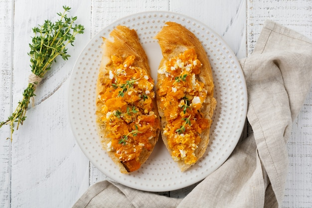 Bruschetta con zucca al forno, feta e timo su superficie in legno chiaro. panino piccante alla zucca. messa a fuoco selettiva.