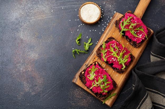 Bruschetta con hummus di barbabietola, rucola e semi di sesamo su una superficie di cemento scuro