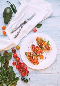 Bruschetta con formaggio, basilico, rucola e pomodorini