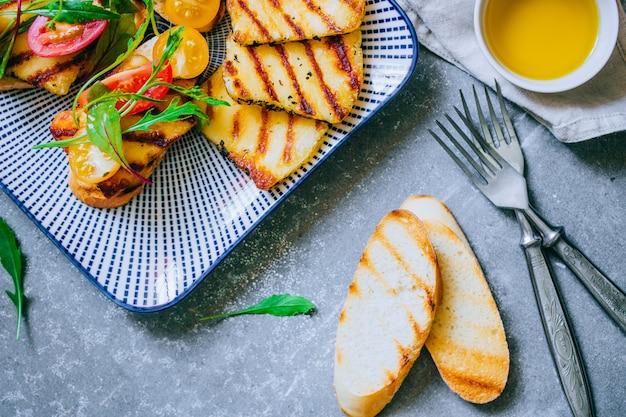 Bruschetta con insalata di pomodorini con formaggio haloumi grigliato