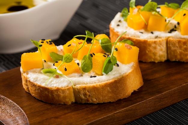 Bruschetta con mango tritato, crescione, basilico e formaggio di capra su baguette fresche sul tavolo