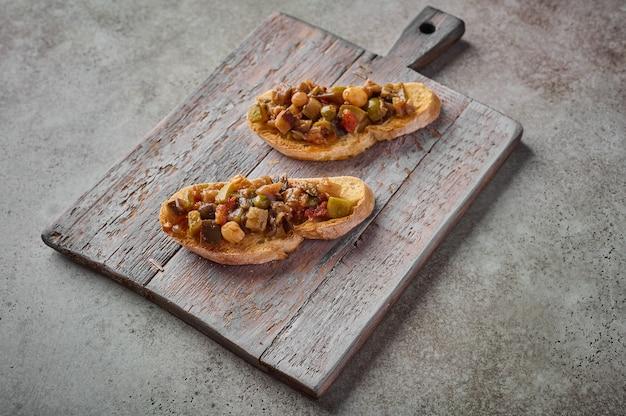 Bruschetta con caponata siciliana tradizionale fatta in casa e pane ciabatta su tagliere di legno. avvicinamento