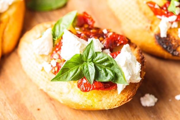 Bruschetta con olio d'oliva, pomodori secchi, feta e basilico fresco