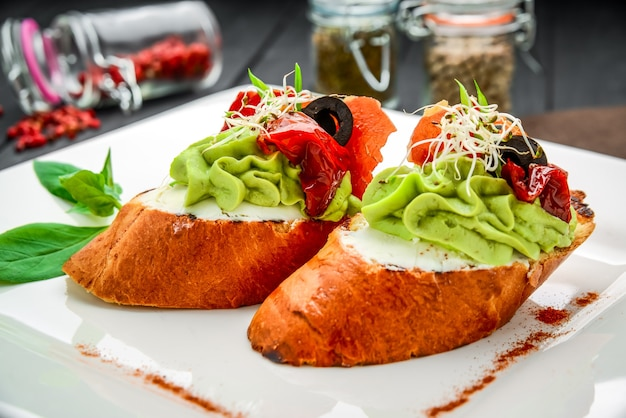 Bruschetta con prosciutto, avocado, pomodori, rucola e parmigiano