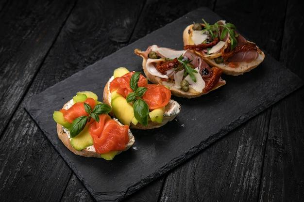 Bruschetta con salmone e carne su un tavolo di legno scuro