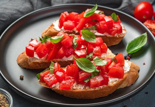 Bruschetta con pomodoro, basilico e primo piano di crema di formaggio. antipasto italiano. vista laterale.