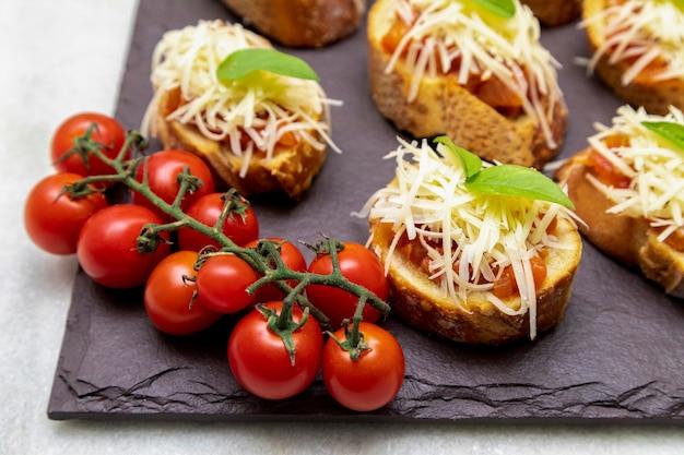 Bruschetta con pomodoro, basilico e parmigiano su tavola di legno.