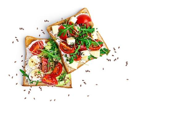 Bruschetta con verdure, uova di quaglia e formaggio su uno sfondo bianco. foto di alta qualità