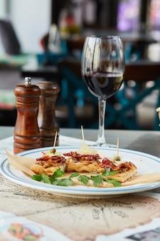 Bruschetta su un tavolo di legno in un piatto bianco e un bicchiere di vino rosso