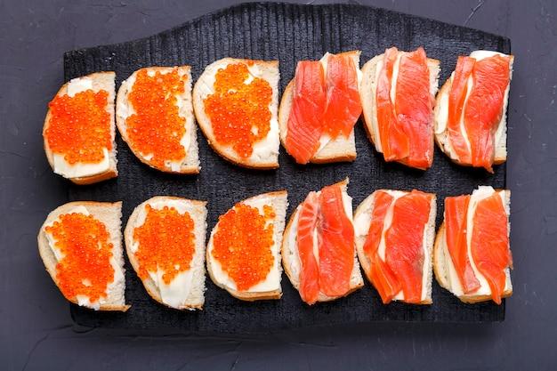 Bruschette con caviale rosso burro e trota su una tavola di legno nera su una superficie grigia