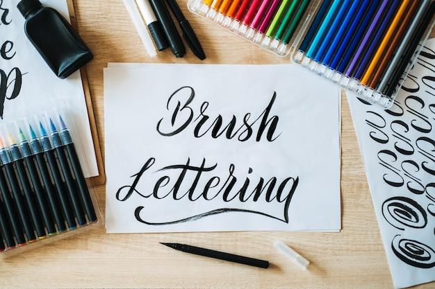Spazzola il testo dell'iscrizione su carta e pennelli e matite colorate sul tavolo l'arte dell'iscrizione e