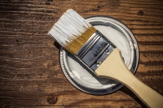 Pennello sul coperchio da sotto la vernice, fondo in legno con spazio di copia.