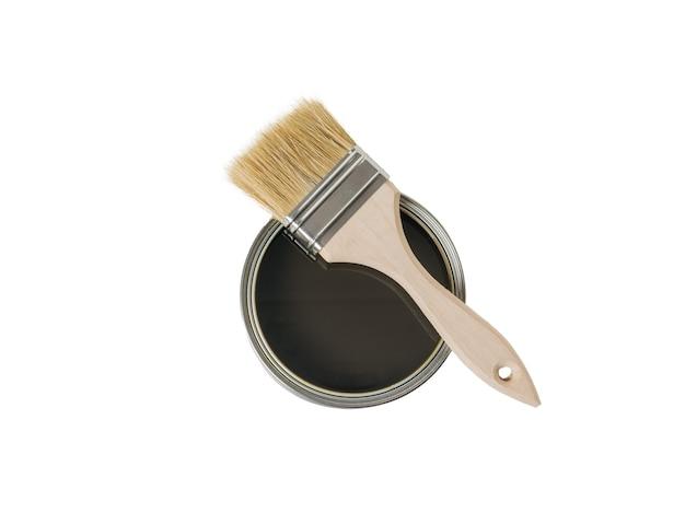 Pennello su un barattolo aperto con una composizione protettiva per legno isolato su una superficie bianca. materiali per la pittura.