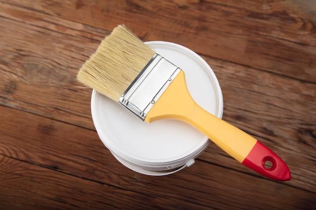 Pennello sulla ciotola di vernice sulla tavola di legno