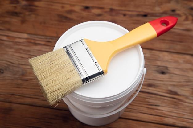 Pennello sulla ciotola della vernice sul tavolo di legno