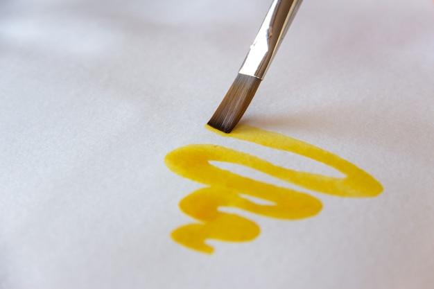 Pennello che dipinge linee curve di inchiostro cinese giallo.