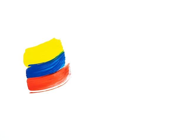 Pittura a pennello su sfondo bianco nei colori giallo, blu e rosso. copia spazio. bandiera colombiana.