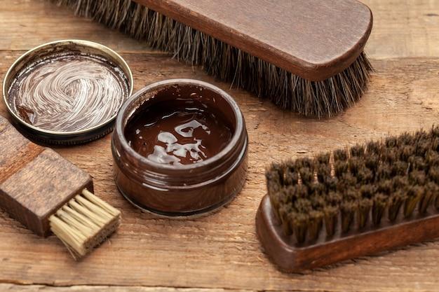 Spazzola per scarpe. pulizia e lucidatura scarpe con spazzole. lucido da scarpe e spazzola su superficie di legno.