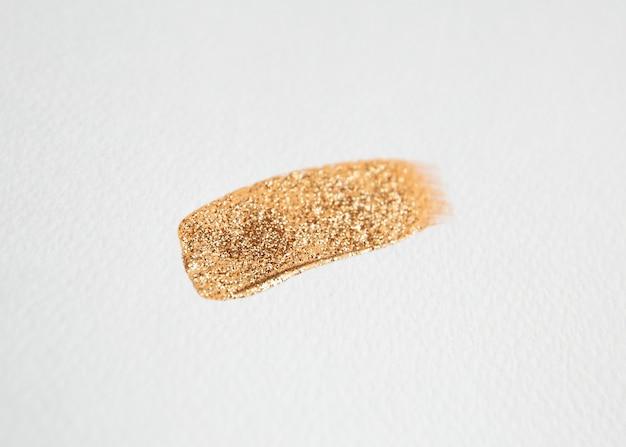 Pennellata di vernice dorata con glitter su carta da acquerello bianca