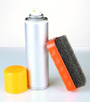 Pennello per scarpe scamosciate e spray di vernice aerosol, su fondo bianco