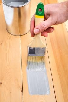 Spazzola con la latta in mano. un uomo dipinge tavole di legno in un pennello grigio.