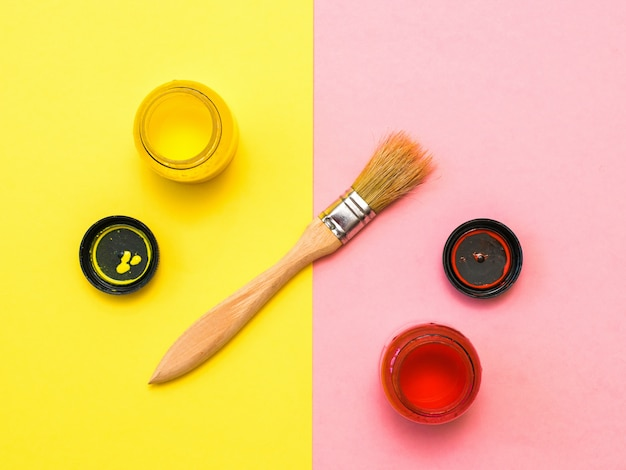 Pennello con tubetti di vernice su un giallo e rosa