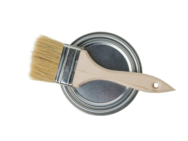 Un pennello con manico in legno su una lattina di vernice di ferro chiusa. materiali per la pittura.
