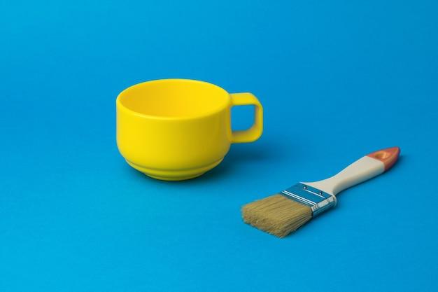 Pennello e una tazza gialla su sfondo blu. la tendenza del colore.