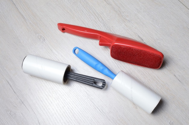 Spazzole per la pulizia dei vestiti. appiccicoso e un pennello a setole, sdraiati su un piano di lavoro di colore chiaro.