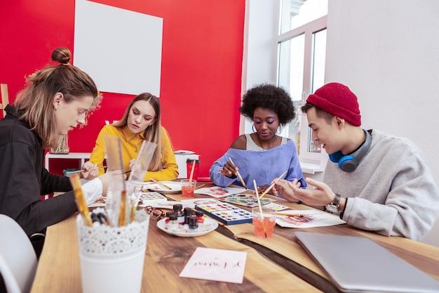 Pennelli e disegno. quattro talentuosi studenti d'arte alla moda che tengono in mano i pennelli mentre disegnano