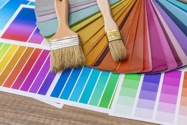 Pennelli e campioni di tavolozza dei colori della vernice su fondo di legno