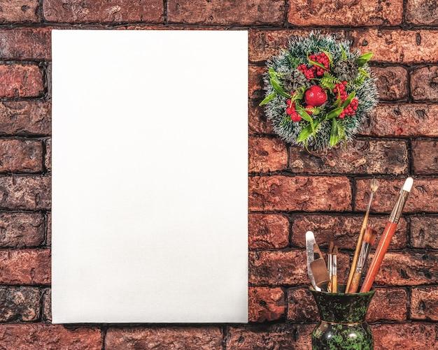 Tavolozza di pennelli con tela bianca e una corona di natale su uno sfondo di muro di mattoni rossi