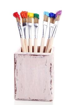 Spazzole con vernici colorate, isolate su superficie bianca