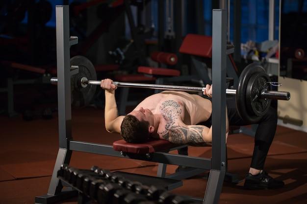 Uomo atletico brutale che pompa i muscoli sulla pressa da banco