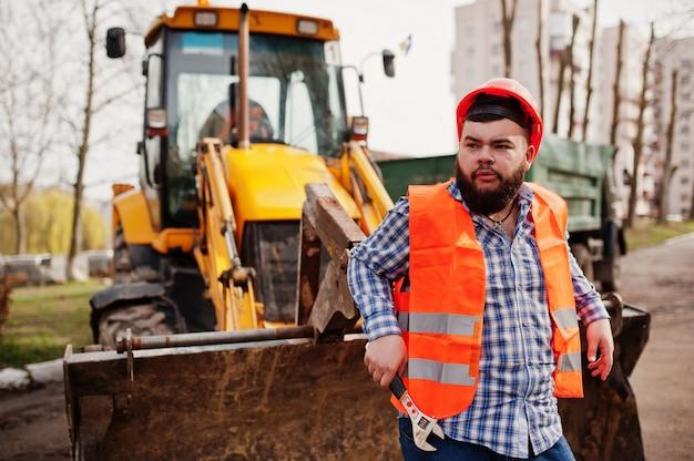 Brutal barba operaio uomo vestito operaio edile in casco di sicurezza arancione, contro traktor con chiave regolabile a portata di mano.