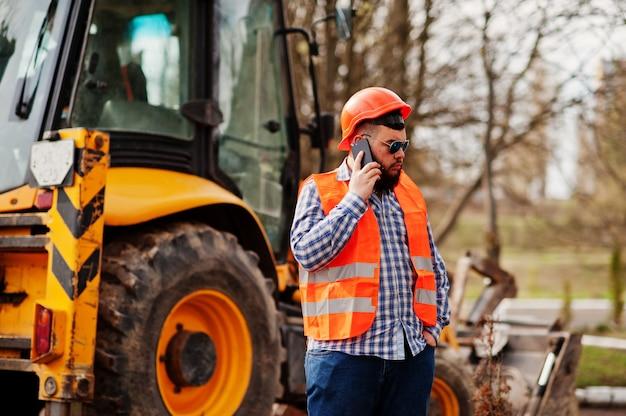 Brutal barba operaio uomo vestito operaio edile in casco di sicurezza arancione, occhiali da sole contro traktor con il telefono cellulare a portata di mano.