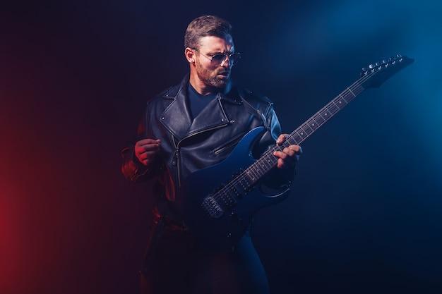 Brutale musicista heavy metal barbuto in giacca di pelle e occhiali da sole sta suonando la chitarra elettrica sul nero