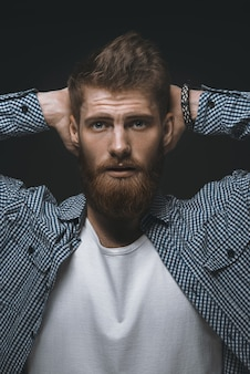 Uomo barbuto brutale che tiene le mani dietro la testa