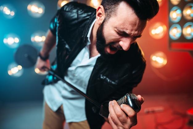 Brutale performer barbuto con microfono canta una canzone sul palco con le decorazioni delle luci